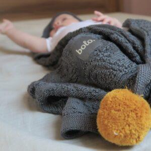leżący na plecach niemowlak owinięty w grafitowy bambusowy kocyk bolo z kapturkiem i pomponami