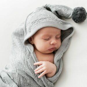 śpiący niemowlak owinięty w szary bambusowy kocyk bolo z kapturkiem i pomponami